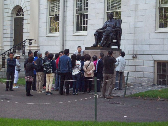 A tour stops at the statue of John Harvard, the benefactor after whom Harvard University was named / Photo taken by Sara Letourneau